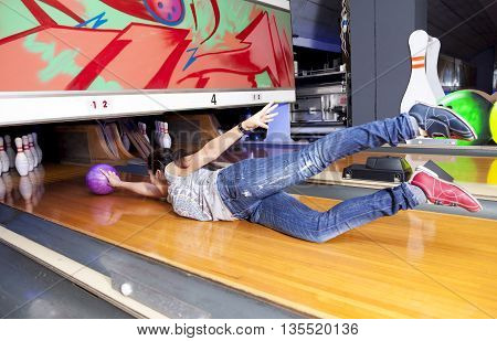 Young Woman Sliding Down A Bowling Alley