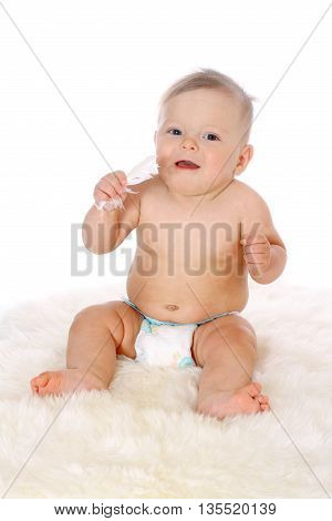 little baby in a diaper sitting in a full-length with a feather in her hand on white fur isolated