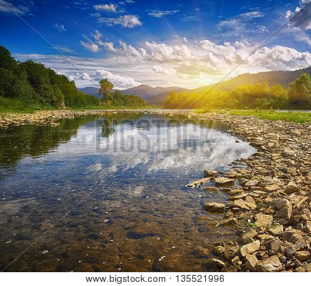 Mountain river stream of water in the rocks with blue sky. Clear river with rocks leads towards mountains lit by sunset