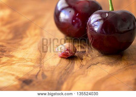 macro cherries with core on olive wood
