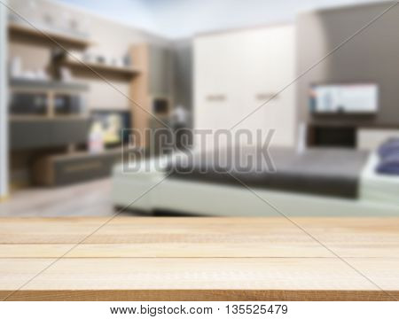 Wooden board empty table in front of blurred background. Perspective light wood over blur in modern comfortable bedroom with white bed. Mock up for display or montage your products