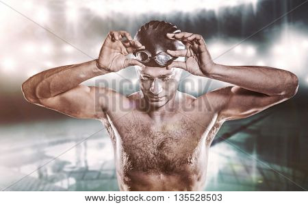 Composite image of swimmer holding swimming goggles against a swimming pool
