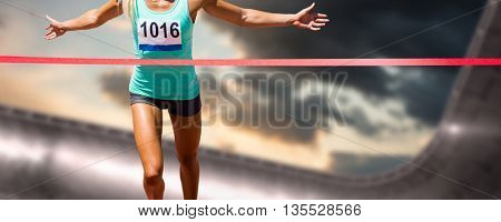 Sportswoman finishing her run against composite image of arena and cloudy sky