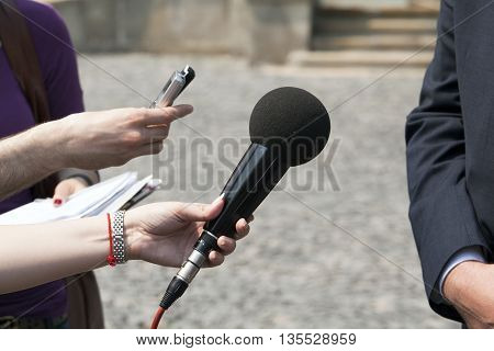 Journalist holding microphone conducting media interview. News conference.