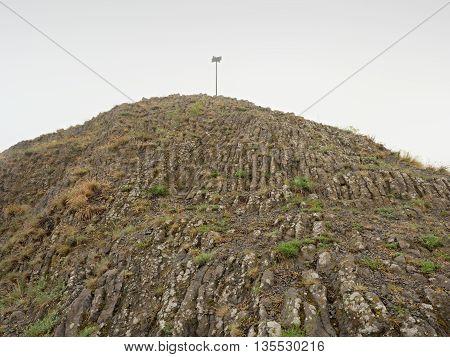 Sharp peak of basalt formation. Long basalt poles of cold volcano.