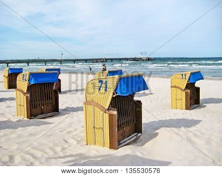 Scharbeutz Germany - May 23 2008: Beach in Scharbeutz with beach chairs along baltic sea coast pier in the background