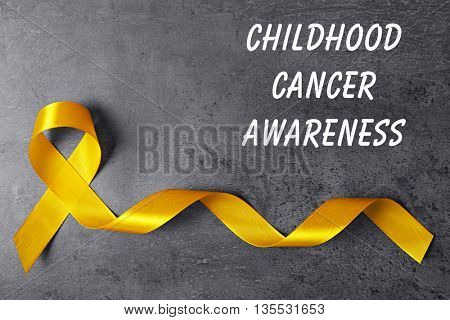 Yellow ribbon and text Childhood Cancer Awareness on grey textured background