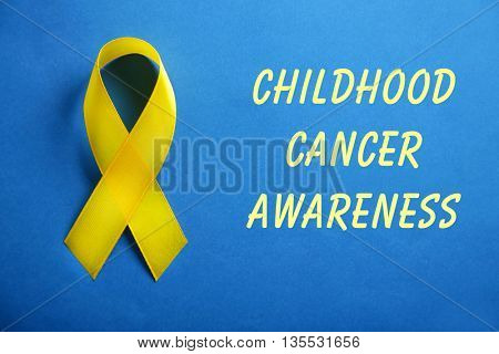 Yellow ribbon and text Childhood Cancer Awareness on blue background