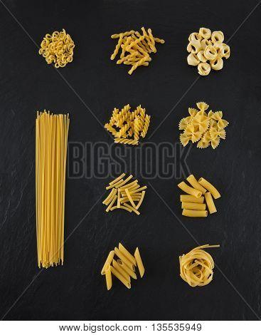 Selection of pasta on black slate background, Spaghetti, Penne, Tagliatelle, Fussili, Gemelli, Maccheroni, Rigatoni, Farfalle, Gobetti, Tortellini
