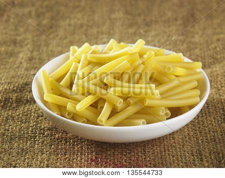 Maccheroni pasta on top of sack cloth