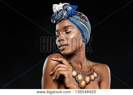 Close-up potrait of a stylish african woman with eyes closed isolated on the black background