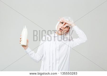 Pretty young woman closed her nose and holding bottle of milk