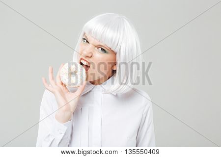 Angry pretty young woman with blonde hair eating fresh donut