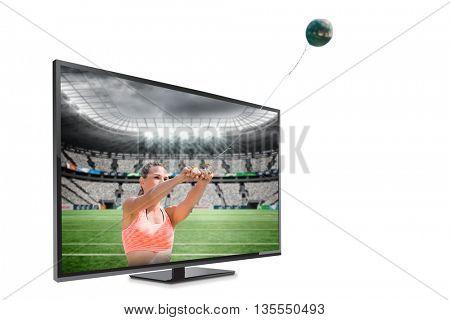 Portrait of sportswoman practising hammer throw against rugby stadium