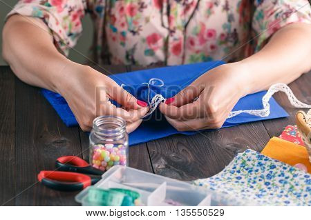 Close-up of woman's hand stitching quilting on dark rustic Wood Background