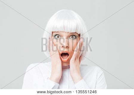 Scared shocked young woman with opened mouth and hands on cheeks over white background