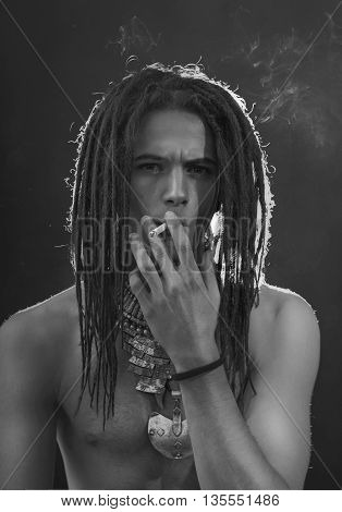 Young man's portrait. Stylish handsome sexy Guy with Dreadlocks and ethnic Jewelry Accessories (necklace bracelet ring) Close-up face. Tribal Style. Trendy youthful man's look
