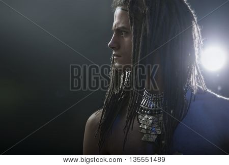 Young man's portrait. Stylish handsome sexy Guy with Dreadlocks and ethnic Jewelry Accessories (necklace) Close-up face. Tribal Style. Trendy youthful man's look warrior. War paint