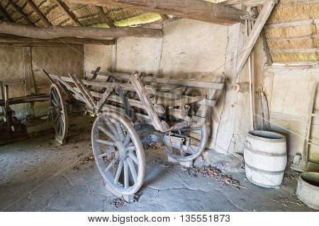 Old wooden horse-drawn cart standing inside a barn.