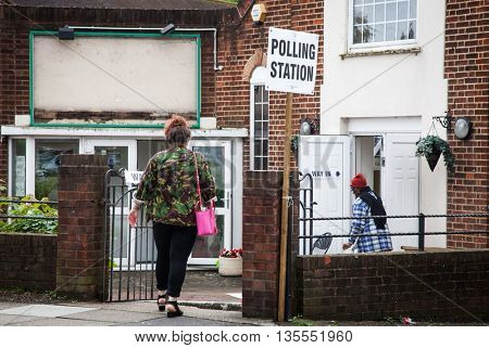 LONDON, UNITED KINGDOM - JUNE 23: A man holding an umbrella passes by a polling station during the British EU Referendum in London, United Kingdom on June 23, 2016.
