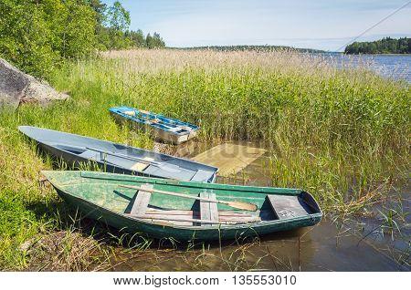 Small Rowboats Lay On The Coast Of Still Lake