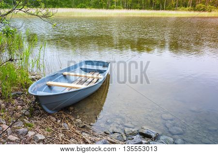 Small Rowboat Lays On Coast Of Still Lake