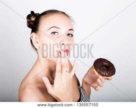 young woman in bright makeup eating a tasty donut with icing. Funny joyful woman with sweets, dessert. dieting concept. junk food. girl licking their fingers.