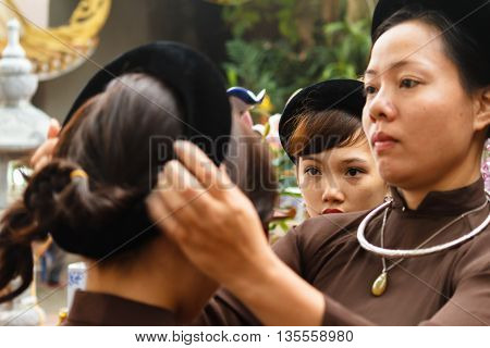 Thanh Hoa, Vietnam - October 19, 2014: A Vietnamese woman fixes girl's hair. They prepare for a spirit mediumship ritual of their religious community (Dao Mau) which they will be attending as guests.