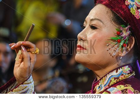 Thanh Hoa, Vietnam - October 19, 2014: A medium smokes while being dressed up to perform a spirit mediumship ritual in Central Vietnam. In trance the medium channels goddesses of the Dao Mau religion.