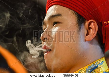 Thanh Hoa, Vietnam - October 19, 2014: A medium smokes while being dressed up to perform Len Dong, a spirit mediumship ritual in Central Vietnam. In trance the medium channels gods and goddesses of the Dao Mau religion.