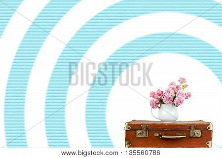 Pink flowers in jug on old brown vintage suitcase. Roses in jug on blue stripes background. Pink roses. Shabby chic. Rustic concept.
