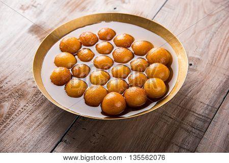 Gulab jamun, or gulaab jamun, is a milk-solids-based sweet mithai poster