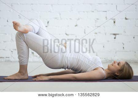 Pregnant Young Woman Doing Prenatal Yoga. Variation Of Shoulder Bridge Exercise