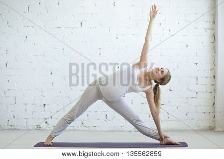 Pregnant Young Woman Doing Prenatal Yoga. Extended Triangle Pose