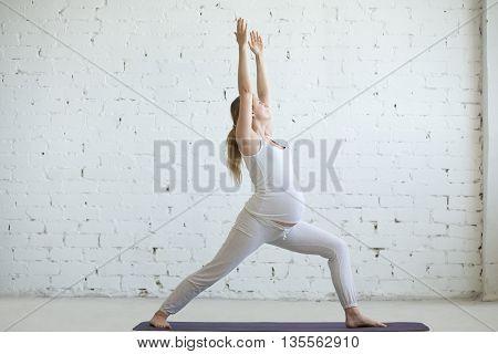 Pregnant Young Woman Doing Prenatal Yoga. Warrior One Pose