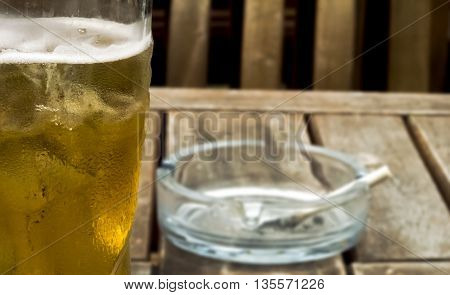 Glass of cold beer and cigarette in ashtray