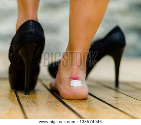 High heels hurts very often, feet with white little patch on ankle, one feet on the floor and other with black shoe.