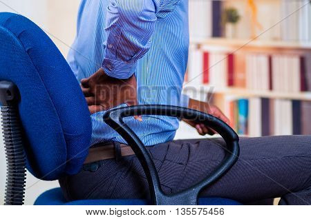 Close up of back pain, man holding his back with one hand.