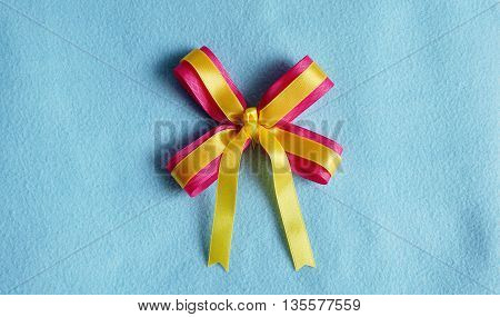 Pink and yellow ribbon on blue fabric background