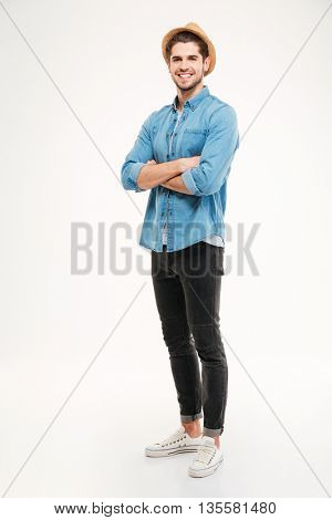 Full length portrait of a smiling casual man standing with hands crossed isolated on a white background