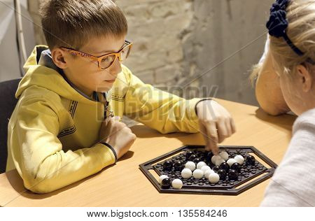 KYIV, UKRAINE - JUN 3, 2016: Unidentified boy in glasses playing Abalone strategy board game with a friend on June 3, 2016. Abalone game designed by Michel Lalet and Laurent Levi in 1987.