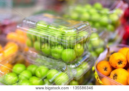 Turkish green plums in plastic containers and orange loquat.