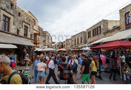 RHODOS, GREECE- JUNE 14 2016: Many tourists visiting and shopping at market street in the old town Rhodos, Greece