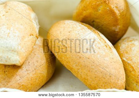 Selection of delicous bread buns lying in basket, as seen from above.