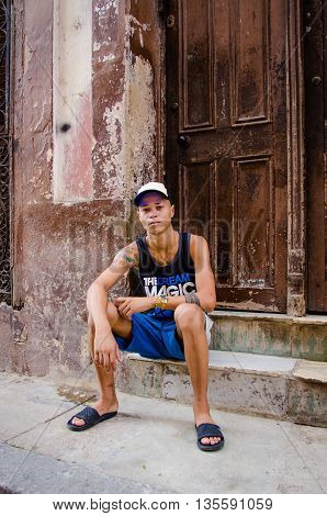 HAVANA - CUBA JUNE 19, 2016: A young man with tattoos  sits on the stoop of his home, one of thousands of deteriorating and decaying buildings in La Habana Vieja.