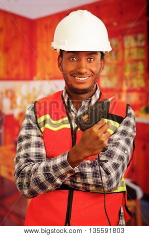 Young engineer carpenter wearing square pattern flanel shirt with red safety vest, holding glue gun smiling to camera.