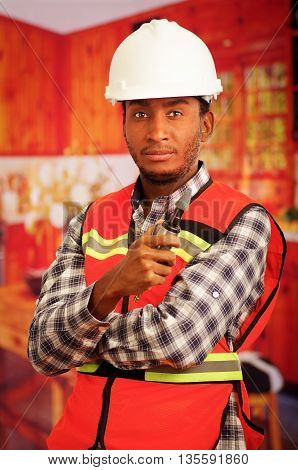 Young engineer carpenter wearing helmet, square pattern flanel shirt with red safety vest, holding small handheld electric polisher tool smiling to camera.