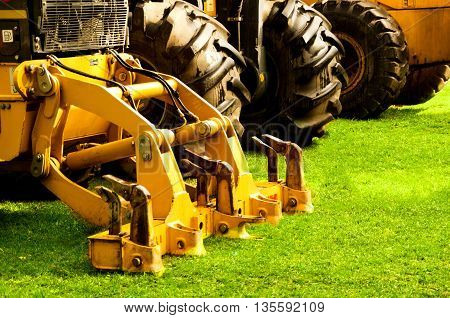 Yellow metal mechanical part attached to bulldozer, heavy duty construction machinery.