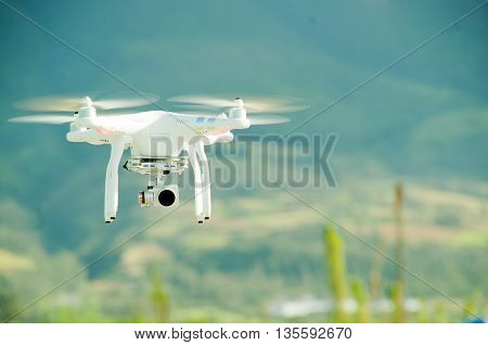 White drone with camera mounted underneath hovering midair, mountain landscape background.