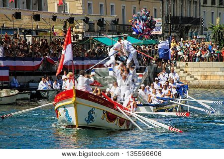 SETE, FRANCE - August 23 2014: Water Jousting performance during St.Louis festival at the streets of Sete South of France on August 23 2014. Saint Louis is the patronal feast of Sete and also the jousters holiday which offers Six days of non-stop festivit